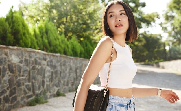Portrait of young stylish asian woman walking on the street, wearing a trendy outfit, turns behind and looking thoughtful