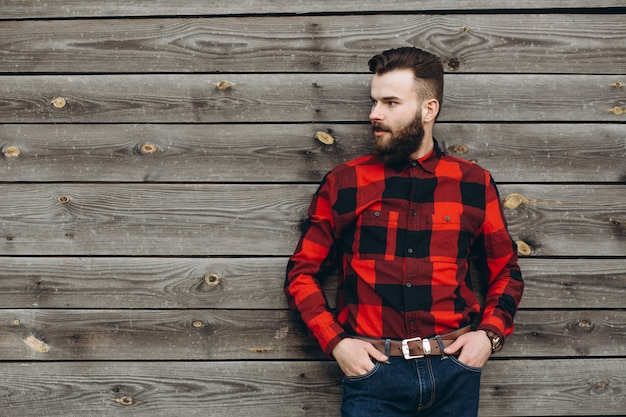 Portrait of a young stylish bearded man dressed up in jeans and a true worker black by red shirt.
