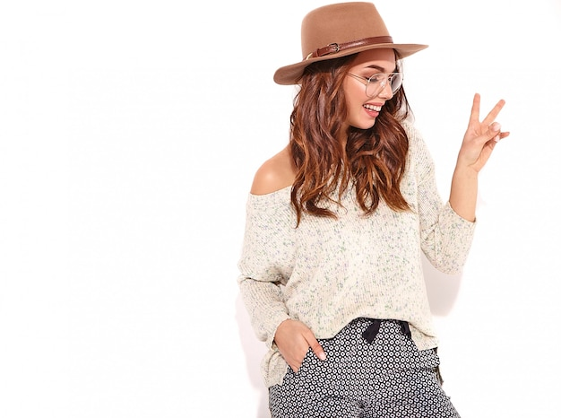 Portrait of young stylish girl model in casual summer clothes in brown hat with natural makeup in glasses isolated. and showing peace sign
