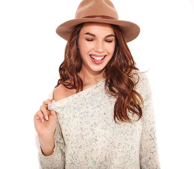 Portrait of young stylish girl model in casual summer clothes in brown hat with natural makeup isolated. ans showing her tongue