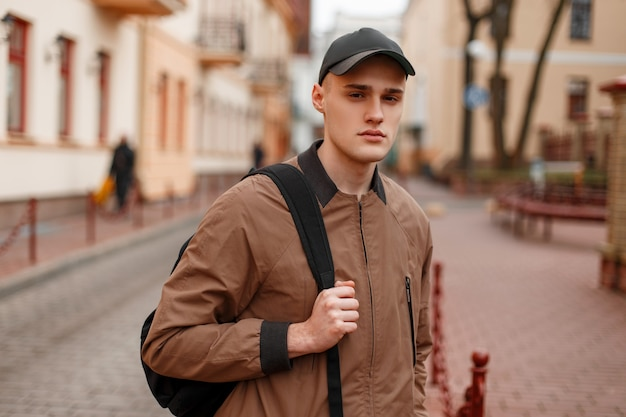 Portrait of a young stylish guy in a fashionable spring beige jacket in a stylish black cap with a sporty trendy backpack in the city