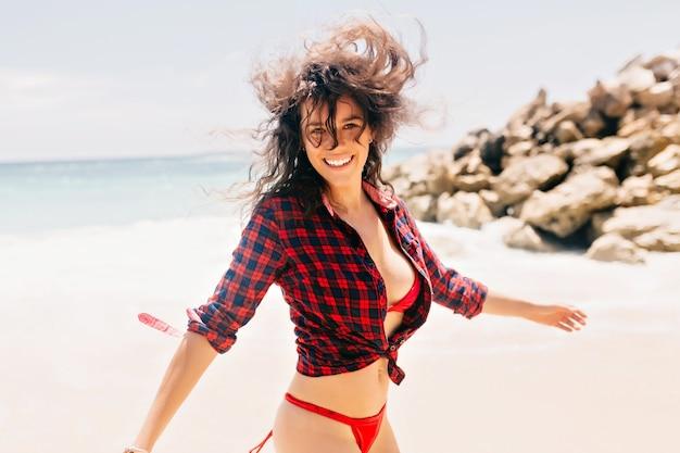 Ritratto di giovane donna alla moda hipster si diverte sulla riva dell'oceano, indossando costume da bagno e camicia