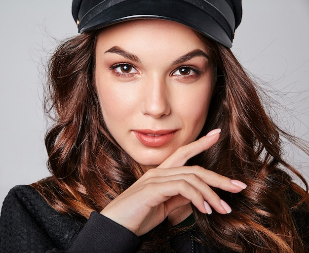 Portrait of young stylish laughing model in black casual summer clothes in cap with natural makeup on gray
