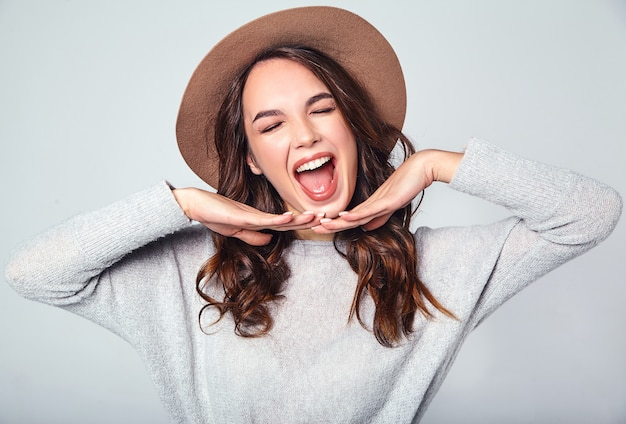 Portrait of young stylish laughing model in gray casual summer clothes in brown hat with natural makeup