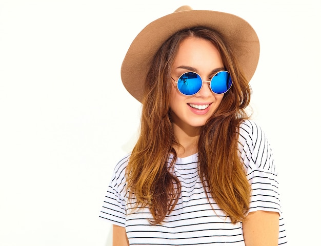 Portrait of young stylish laughing woman model in casual summer clothes in brown hat isolated on white wall