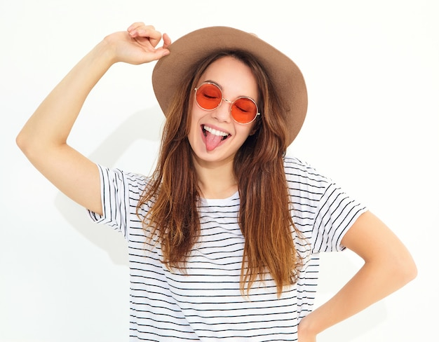 Portrait of young stylish laughing woman model in casual summer clothes in brown hat with natural makeup isolated on white wall. showing her tongue