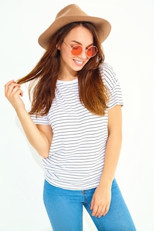 Portrait of young stylish laughing woman model in casual summer clothes in brown hat with natural makeup isolated on white wall