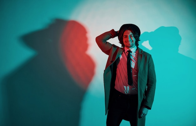 Portrait of young stylish man in hat, suit and tie that stands in neon lights in the studio.