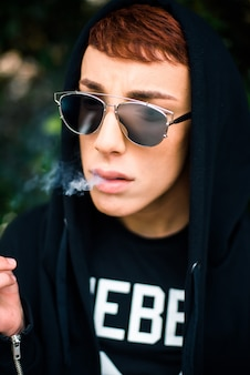 Portrait of a young stylish man wearing sunglasses and hood smoking cigarette