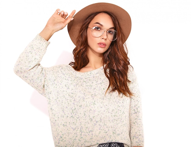 Portrait of young stylish model in casual summer clothes in brown hat with natural makeup in glasses on white