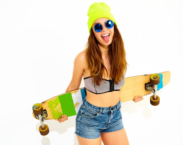 Portrait of young stylish smiling woman model in casual summer swimwear clothes and yellow beanie posing with longboard desk. isolated on white, showing her tongue