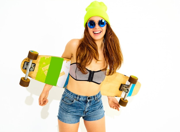 Portrait of young stylish smiling woman model in casual summer swimwear clothes and yellow beanie posing with longboard desk. isolated on white