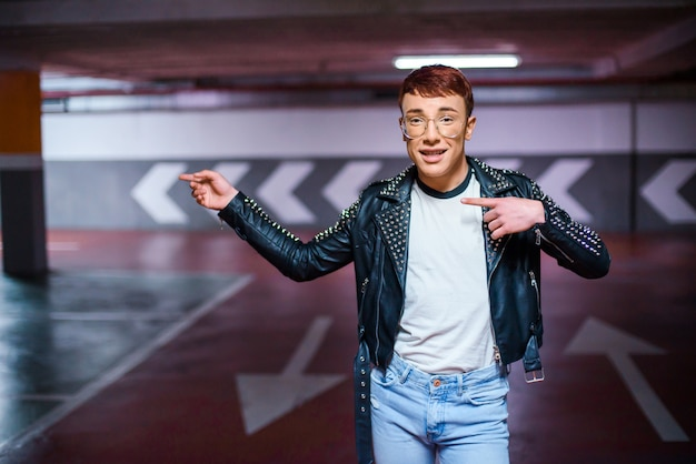 Portrait of a young stylish weared man pointing at something on an underground parking