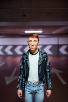 Portrait of a young stylish weared man posing on an underground parking