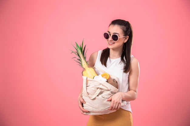 Portrait of a young stylish woman dressed in summer clothes and sunglasses, holding an eco-fruit bag, on pink isolated.