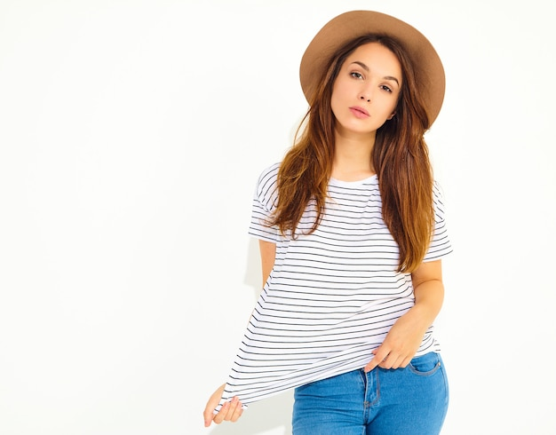 Portrait of young stylish woman model in casual summer clothes in brown hat with natural makeup isolated on white wall