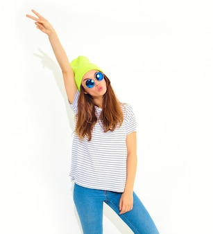 Portrait of young stylish woman model in casual summer clothes in yellow beanie hat isolated on white. hands in air