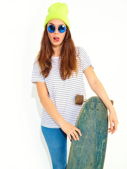 Portrait of young stylish woman model in casual summer clothes in yellow beanie hat posing with longboard desk. isolated on white