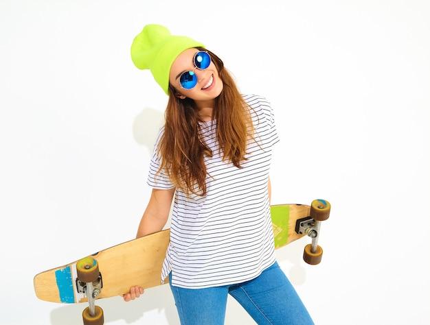 Il ritratto di giovane modello alla moda della donna in estate casuale copre in cappello giallo del beanie che posa con lo scrittorio di longboard. isolato su bianco