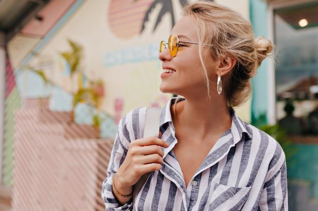 Ritratto di giovane donna alla moda che cammina sulla strada