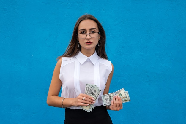 Portrait of young success business woman hold lot of money dollar bills isolated on blue