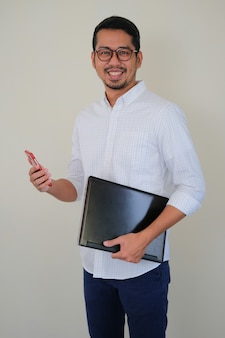 Portrait of young successful asian business man smiling proud while holding laptop and smartphone