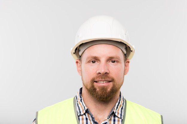 Portrait of young successful builder in white hardhat, checkered shirt and yellow vest standing in front of camera