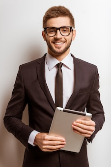 Portrait of a young successful businessman is using tablet.