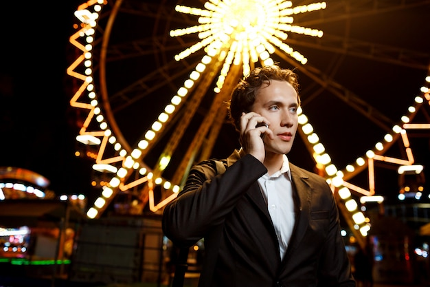 Portrait of young successful businessman over night amusement park. shallow dof