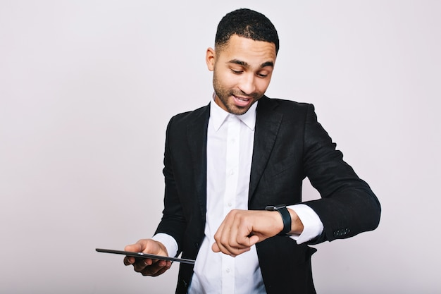 Portrait young successful  busy man in white shirt, black jacket, with tablet looking at watch. stylish businessman, being busy, time for work, meeting, leadership.