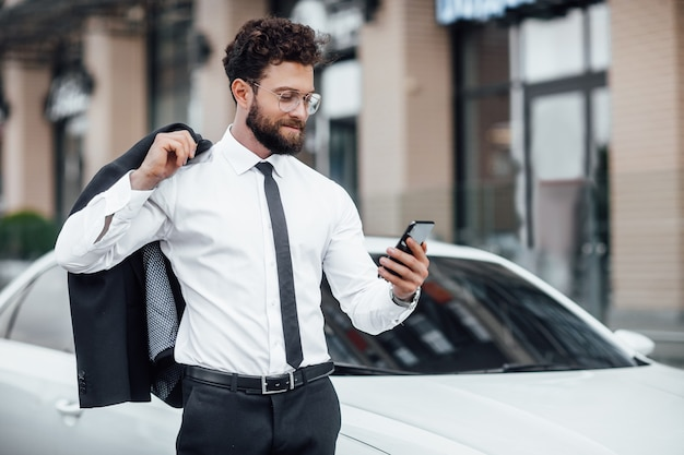 Portrait of a young, successful, handsome man in a suit on the background of a new white car, reading mail on his smartphone
