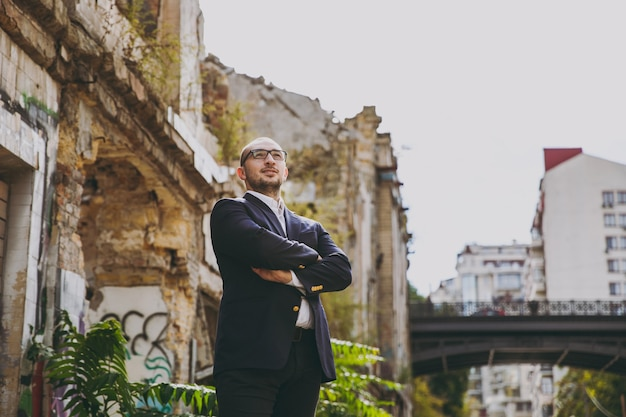 Portrait of young successful smart businessman in white shirt, classic suit, glasses. man standing, holding hands crossed near ruins, debris, stone building outdoors. mobile office, business concept.