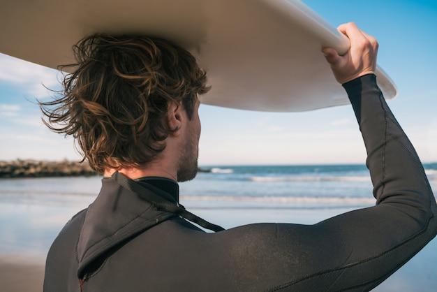 Ritratto di giovane surfista in spiaggia tenendo in mano la sua tavola da surf e indossa una tuta nera da surf. sport e sport acquatici concetto.