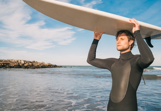 Portrait of young surfer at the beach holding up his surfboard and wearing a black surfing suit. sport and water sport concept.