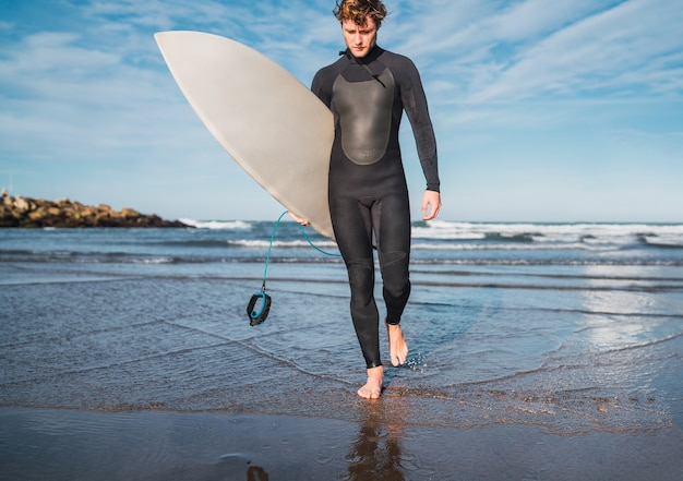 Portrait of young surfer leaving the water with surfboard under his arm. sport and water sport concept.