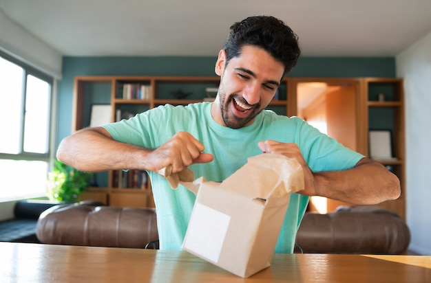 Portrait of a young surprised man opening a gift box while sitting on couch at home.
