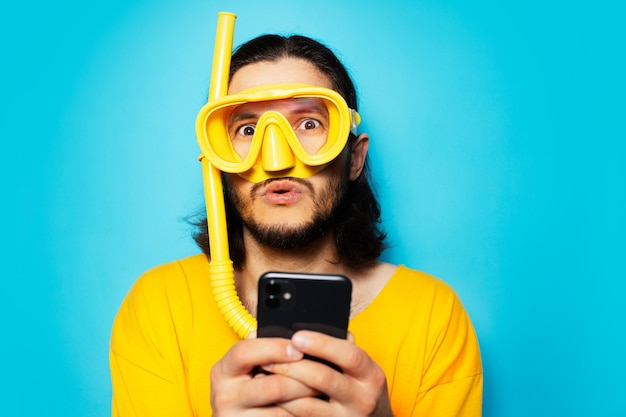 Portrait of young surprised man in yellow, wearing diving mask with snorkel, using smartphone