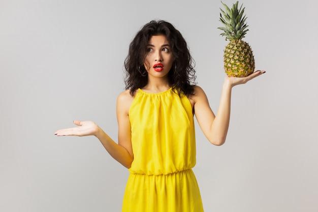 Ritratto di giovane donna graziosa sorpresa in vestito giallo, che tiene ananas, emozione divertente, espressione del viso scioccato, stile estivo, dieta a base di frutta, razza mista, isolato, alzando le mani