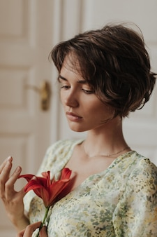 Portrait of young tanned short-haired woman in stylish green and yellow dress looking down and holding red flower