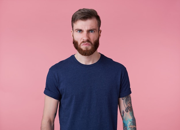 Portrait of young tattooed angry red bearded man in blank t-shirt, frowning and looks at the camera with disgusted, stands over pink background.