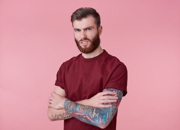 Portrait of young tattooed disgusted red bearded man in blank t-shirt, stands with crossed arms over pink background, frowning and looks at the camera.