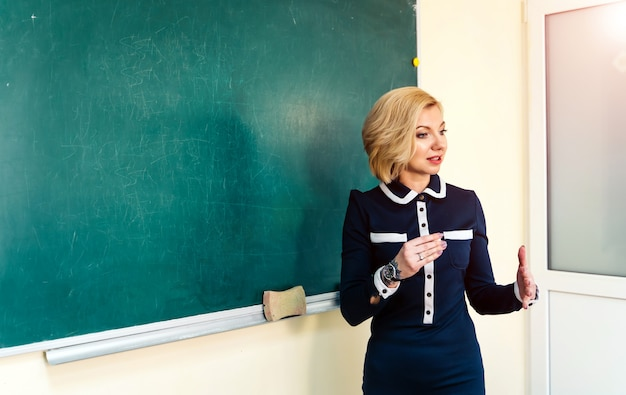 Portrait of young teacher by the blackboard