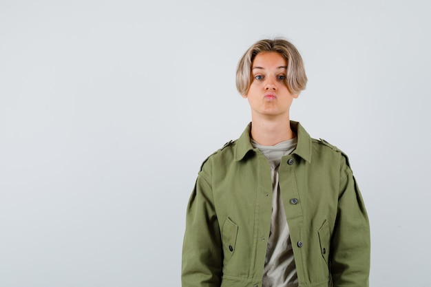 Ritratto di giovane ragazzo adolescente che tiene le labbra piegate in maglietta