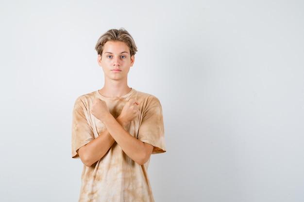 Ritratto di un giovane ragazzo adolescente che mostra un gesto di protesta in maglietta e sembra una seria vista frontale