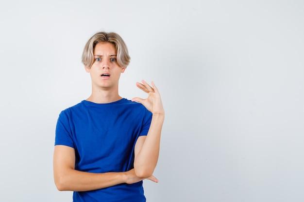 Ritratto di giovane ragazzo adolescente che mostra un cartello di piccole dimensioni con una maglietta blu e sembra scioccato in vista frontale