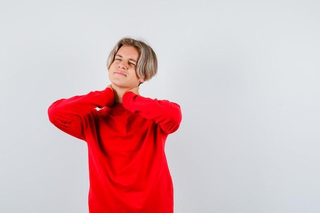 Ritratto di giovane ragazzo adolescente che soffre di dolore al collo in maglione rosso e sembra infastidito vista frontale