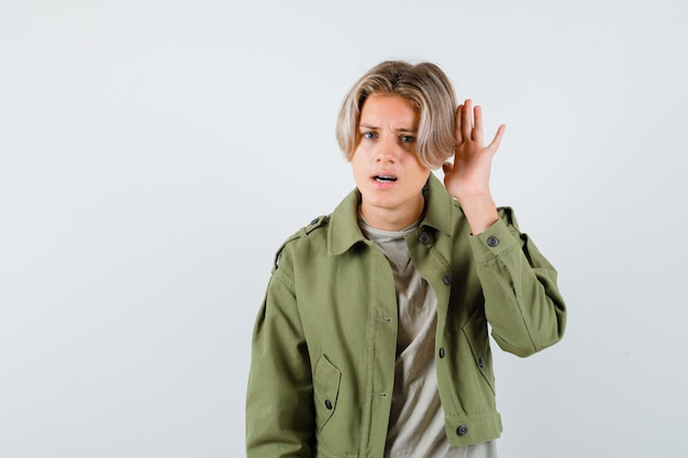 Portrait of young teen boy with hand behind ear in green jacket and looking confused front view