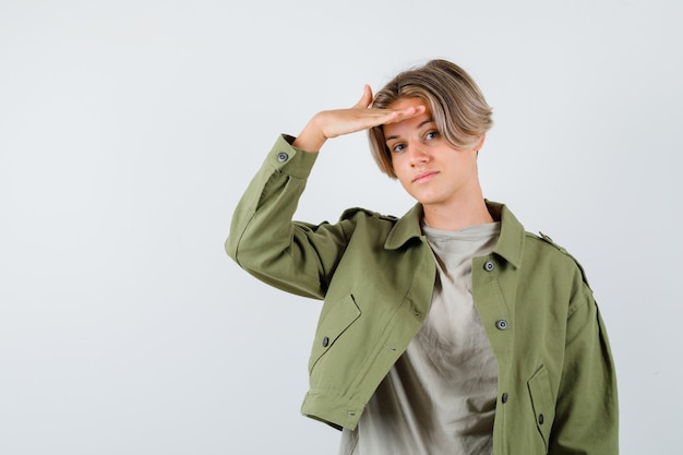 Portrait of young teen boy with hand over head in green jacket and looking confident front view