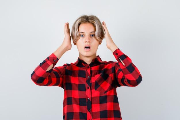Ritratto di giovane ragazzo adolescente con le mani vicino alla testa in camicia a quadri e guardando la vista frontale scioccata