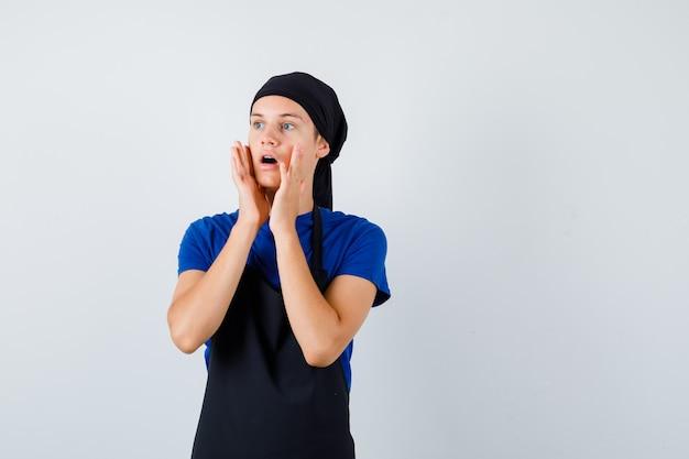 Ritratto di giovane cuoco adolescente con le mani vicino alla bocca aperta in maglietta, grembiule e vista frontale scioccata